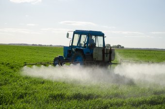 Tractor on a field spraying pesticide